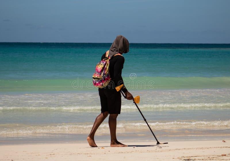 Playa de Macao, Bavaro, República Dominicana, el 10 de abril de 2019/hombre con el detector de metales que busca la playa para la fotos de archivo