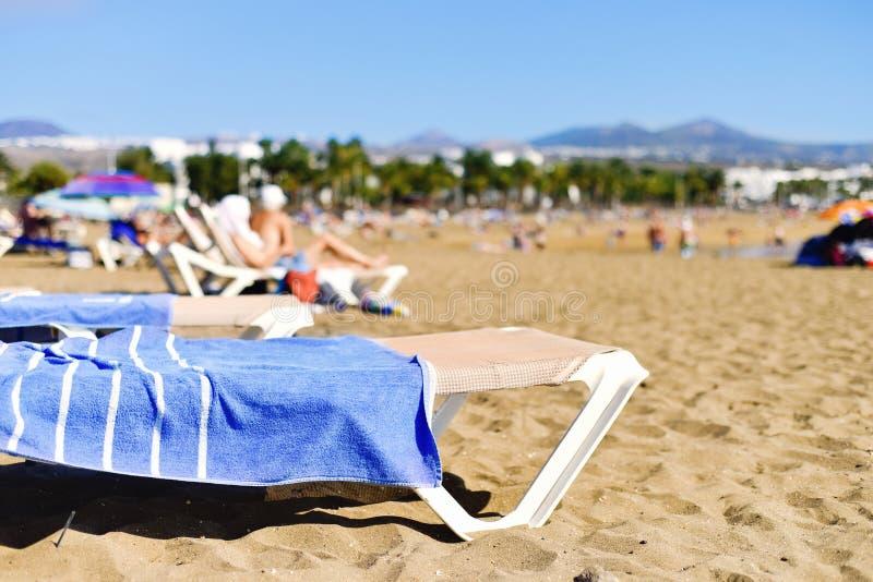 Playa de Matagorda beach in Lanzarote, Spain. Unrecognizable people sunbathing at the Playa de Matagorda beach in Puerto del Carmen, Lanzarote, in the Canary royalty free stock photos