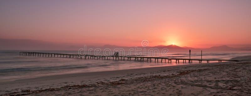 Playa de muro, alcudia, Μαγιόρκα, Ισπανία, ανατολή πέρα από τα βουνά, απομονωμένη παραλία αποβαθρών/λιμενοβραχιόνων στοκ φωτογραφίες