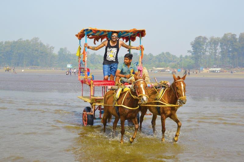 PLAYA DE NAGAON, MAHARASHTRA, LA INDIA 13 DE ENERO DE 2018 Los turistas disfrutan de un paseo del carro del caballo imagen de archivo