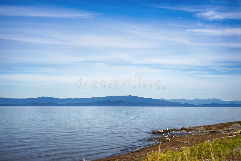 Playa de Qualicum en la isla de Vancouver, con las montañas rocosas canadienses adentro imagenes de archivo