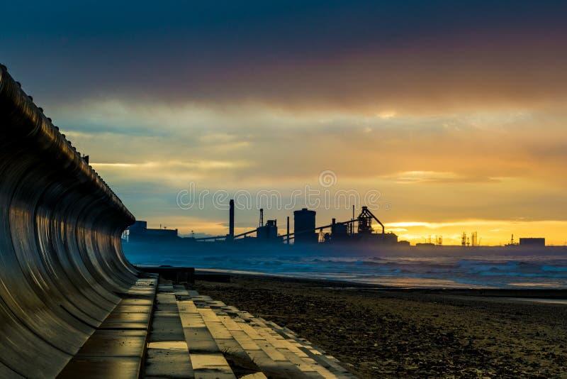 Playa de Redcar en la puesta del sol Fondo industrial imagen de archivo libre de regalías