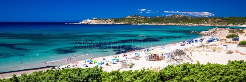 Playa de Rena Majore de los di de Spiaggia con agua y las montañas claras azules, Rena Majore, Cerdeña, Italia imagen de archivo libre de regalías