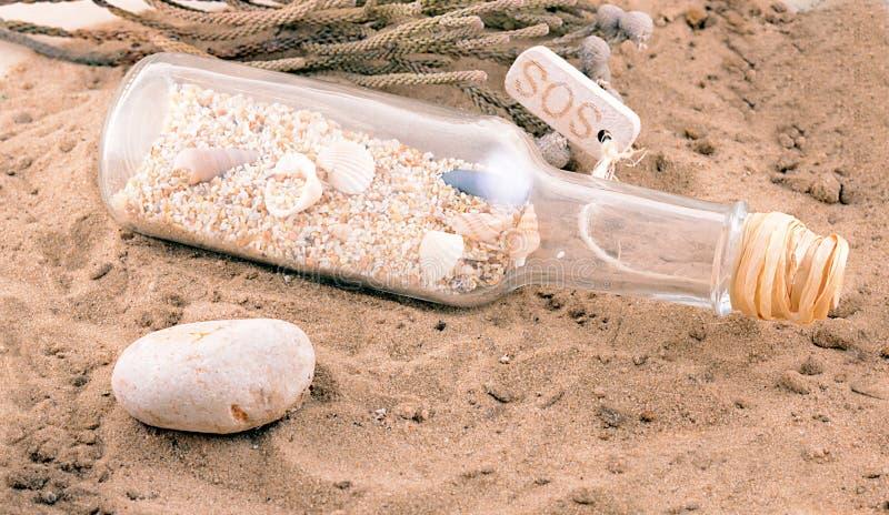 Playa de Sandy con la letra en botella y cáscaras fotografía de archivo libre de regalías