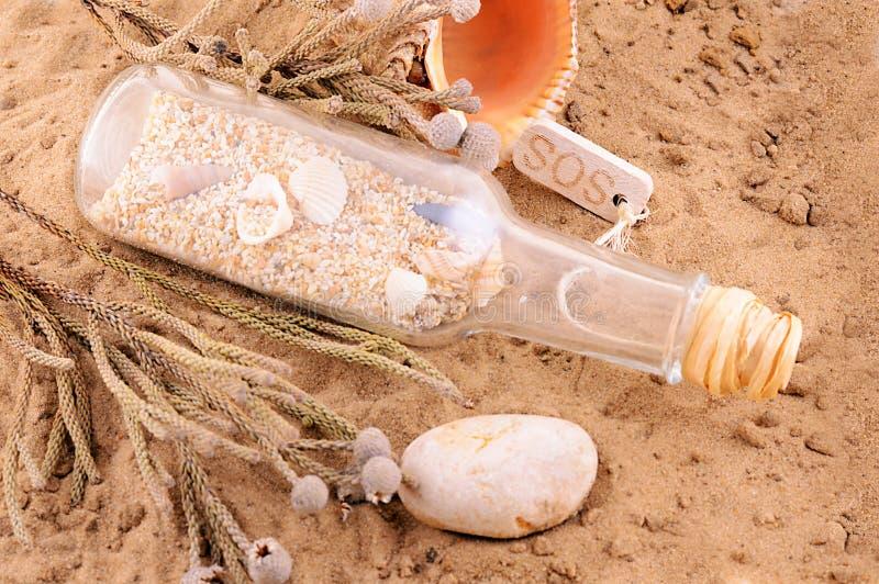 Playa de Sandy con la letra en botella y cáscaras foto de archivo