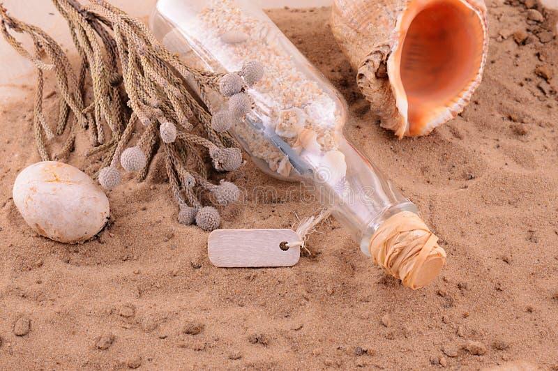 Playa de Sandy con la letra en botella y cáscaras imagen de archivo libre de regalías