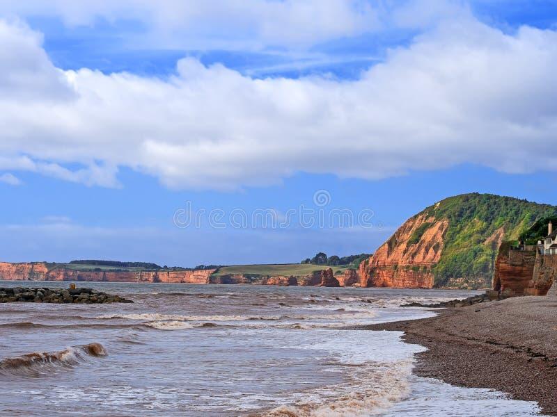 Playa de Sidmouth, Devon, Inglaterra Visión hacia la bahía de Ladram, acantilados rojos en sol del verano tardío En la costa jurá fotografía de archivo libre de regalías
