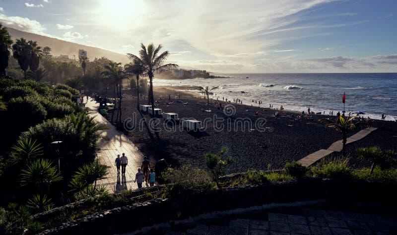 Playa del卡斯蒂略,普埃尔托德拉克鲁斯,特内里费岛,西班牙- 2018年10月30日:人们夺取了走在日落在黑沙子 图库摄影
