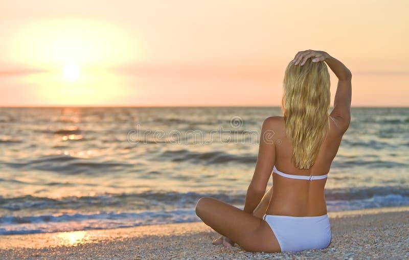 Playa del bikiní de la puesta del sol de la salida del sol de la muchacha de la mujer que se sienta foto de archivo