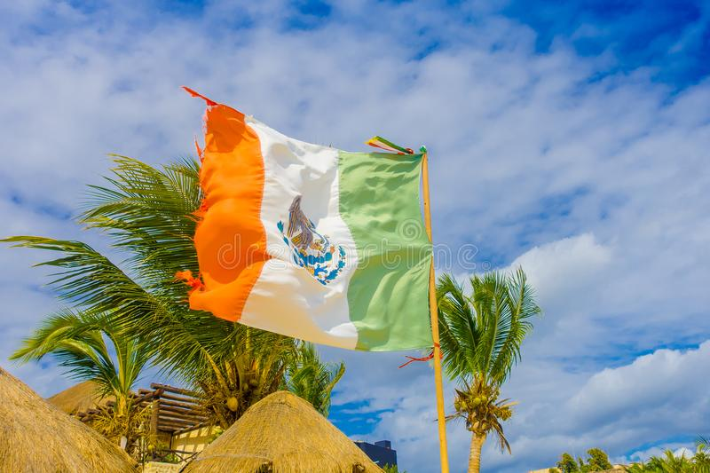 Playa del Carmen, Mexico - January 10, 2018: Outdoor view of a Mexican flag waving in Caribbean beach at Playa Del. Carmen in Mexico royalty free stock photography