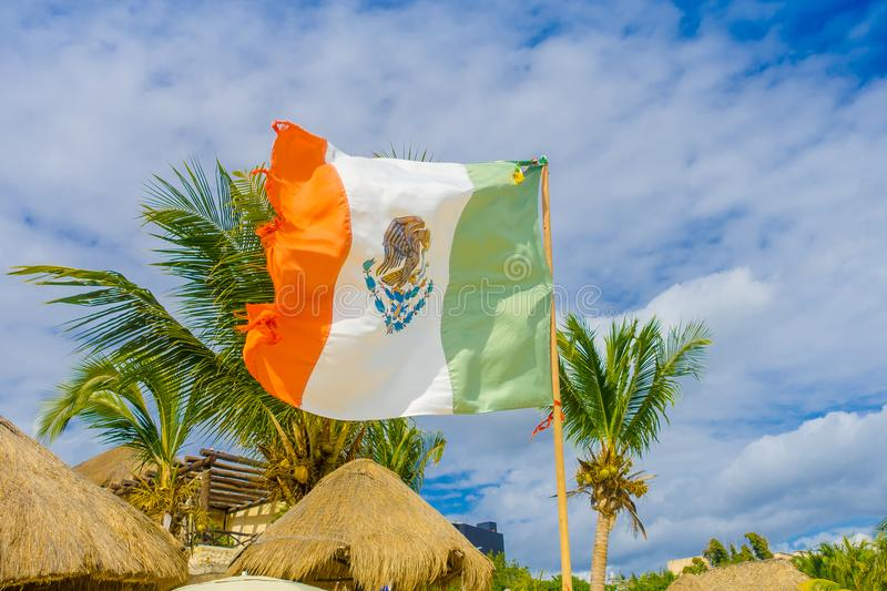 Playa del Carmen, Mexico - January 10, 2018: Outdoor view of a Mexican flag waving in Caribbean beach at Playa Del. Carmen in Mexico royalty free stock images