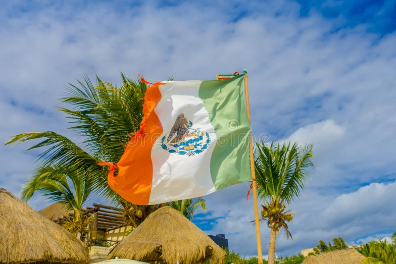 Playa del Carmen, Mexico - January 10, 2018: Outdoor view of a Mexican flag waving in Caribbean beach at Playa Del. Carmen in Mexico royalty free stock photo