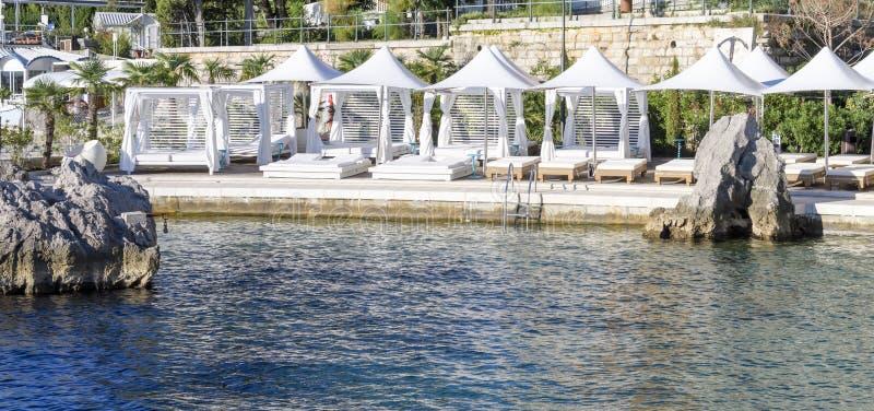 Playa del centro turístico de lujo con las camas, los colchones y las sombrillas blancas imagenes de archivo