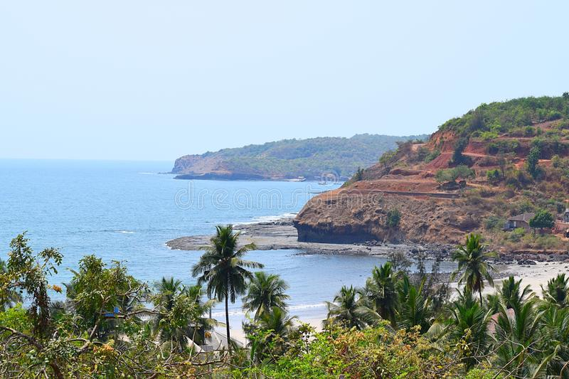 Playa del Mar Arábigo con las colinas y las palmeras, playa de Velaneshwar, Ratnagiri, maharashtra, la India - un fondo natural imágenes de archivo libres de regalías