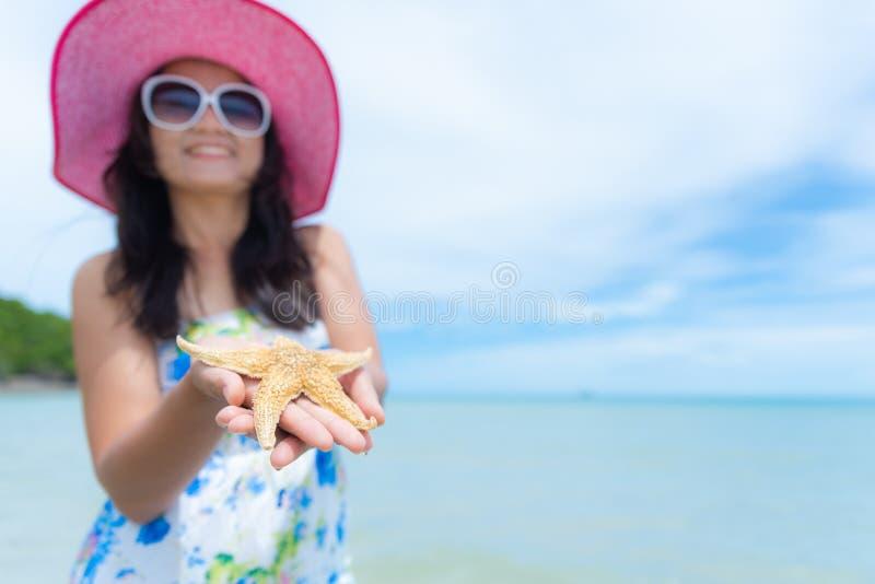 Playa del sombrero de la mujer hermosa y gafas de sol y estrellas de mar el sostenerse que llevan fotografía de archivo libre de regalías