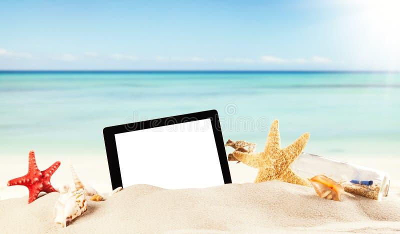 Playa del verano con la tableta en arena imágenes de archivo libres de regalías