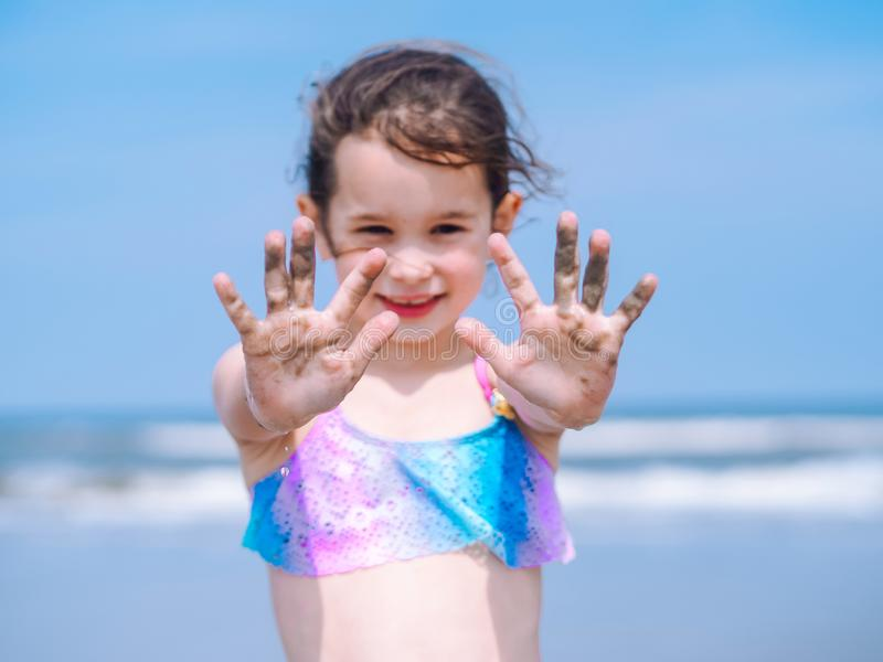 Playa del verano - la niña tiene un buen rato de la playa del centro turístico Ni?o que juega en la playa arenosa Foco en la mano imagenes de archivo