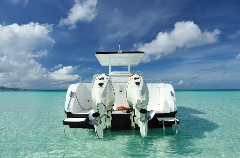 Playa hermosa con el barco de motor imagenes de archivo