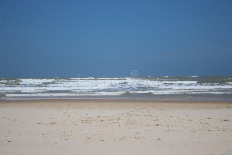 Playa hermosa con el cielo azul claro, las ondas y la arena blanca fotografía de archivo