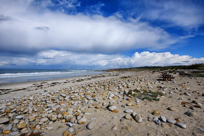 Playa hermosa con la arena y las rocas imagenes de archivo