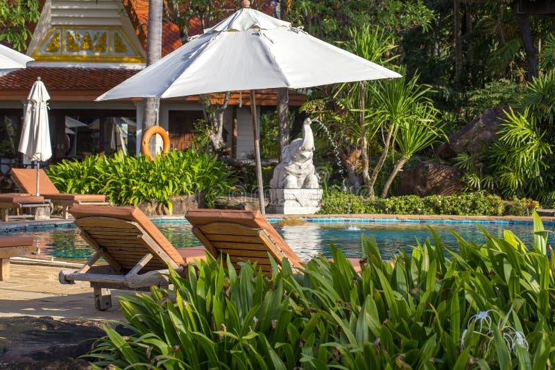 Playa hermosa con la piscina, las palmeras, los daybeds y el paraguas en un jardín tropical cerca del mar fotos de archivo
