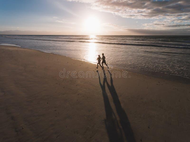 Playa hermosa con los pares del corredor que corren en la orilla imagen de archivo