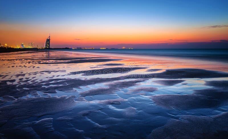 Playa hermosa en puesta del sol imagenes de archivo