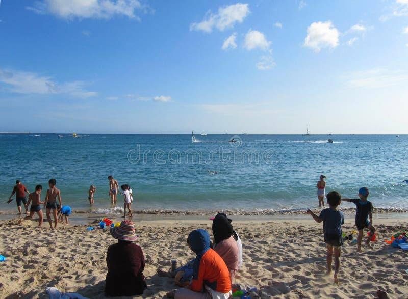Playa hermosa Las mujeres musulmanes están descansando sobre la arena en ropa y sombreros foto de archivo