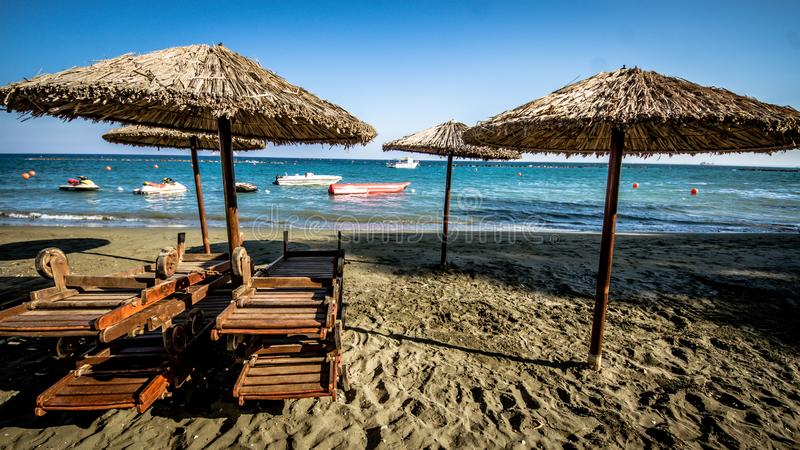 Playa hermosa Sunbeds con el paraguas en la playa arenosa cerca del mar Concepto de las vacaciones de verano y de las vacaciones  fotos de archivo
