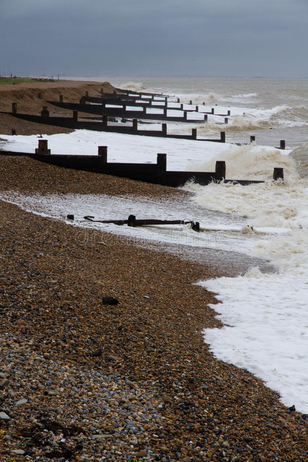 Playa inglesa tempestuosa con rompeolas fotos de archivo