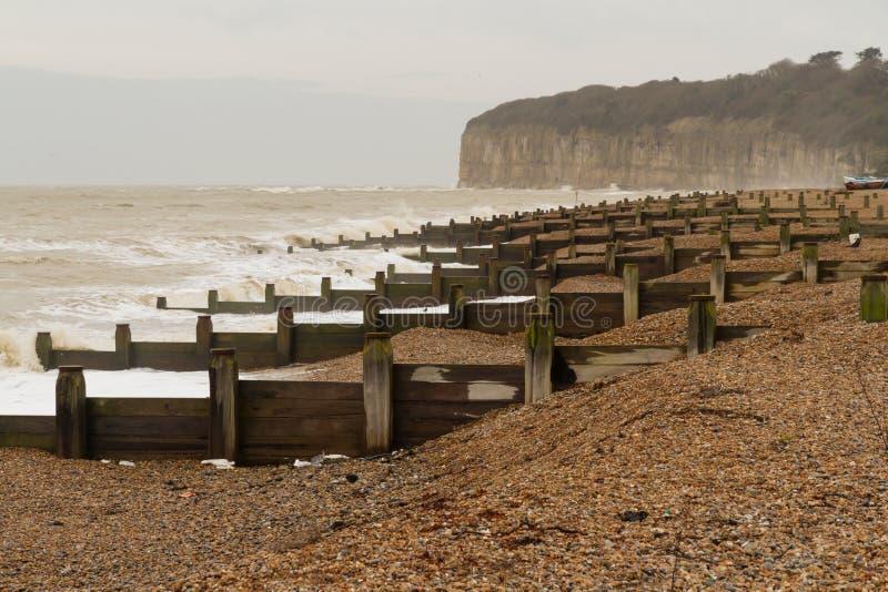 Playa inglesa tempestuosa con rompeolas imagen de archivo libre de regalías