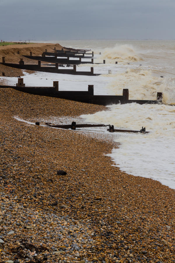Playa inglesa tempestuosa con rompeolas imagenes de archivo