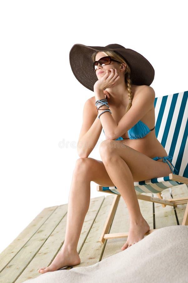 Playa - la mujer joven en bikiní se sienta en silla de cubierta fotografía de archivo