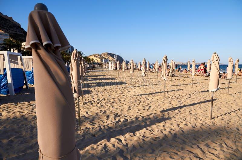 Playa mediterránea con algunos paraguas doblados foto de archivo