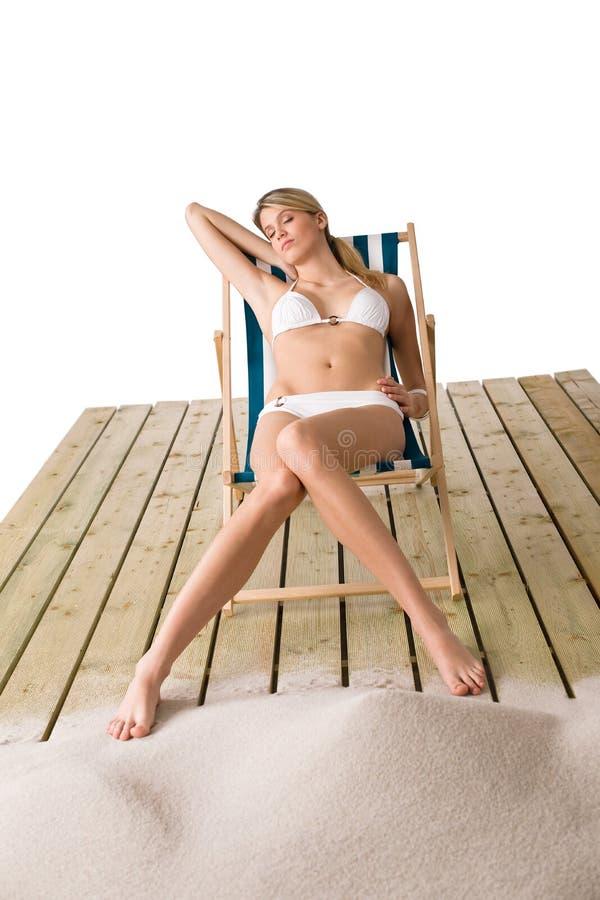 Playa - mujer en bikiní que toma el sol en silla de cubierta fotos de archivo