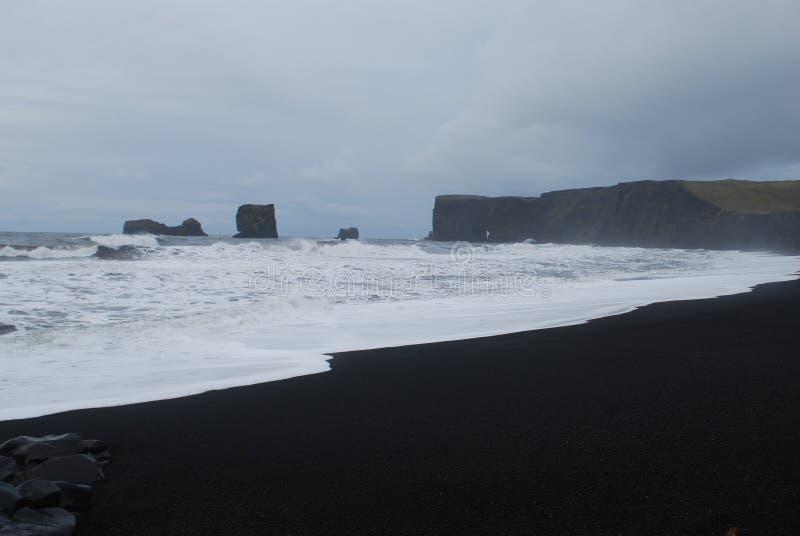 Playa negra de la arena en Islandia fotos de archivo