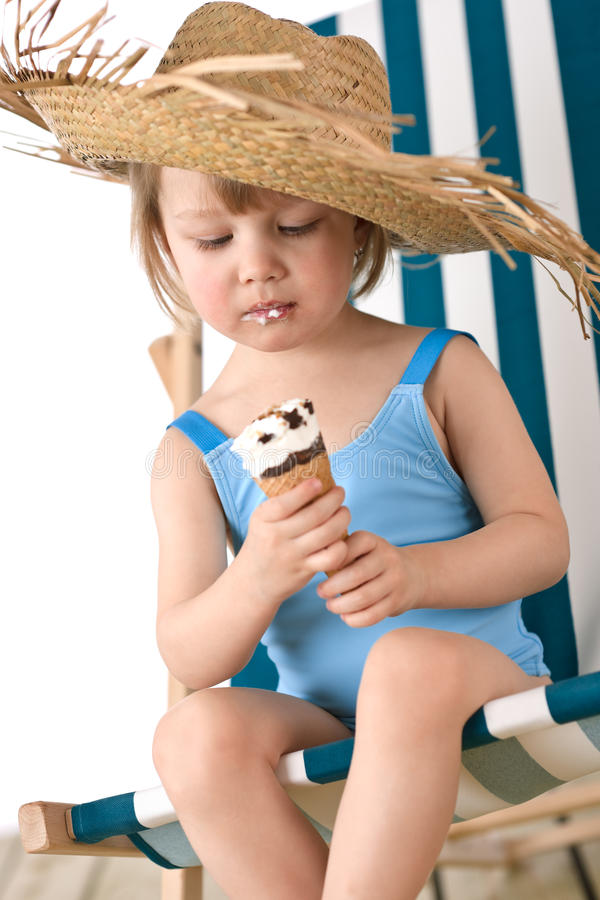 Playa - niña en cubierta-silla con helado foto de archivo