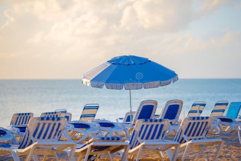 Playa pública en un centro turístico popular en el Caribe con los paraguas y los calesa-salones imagen de archivo
