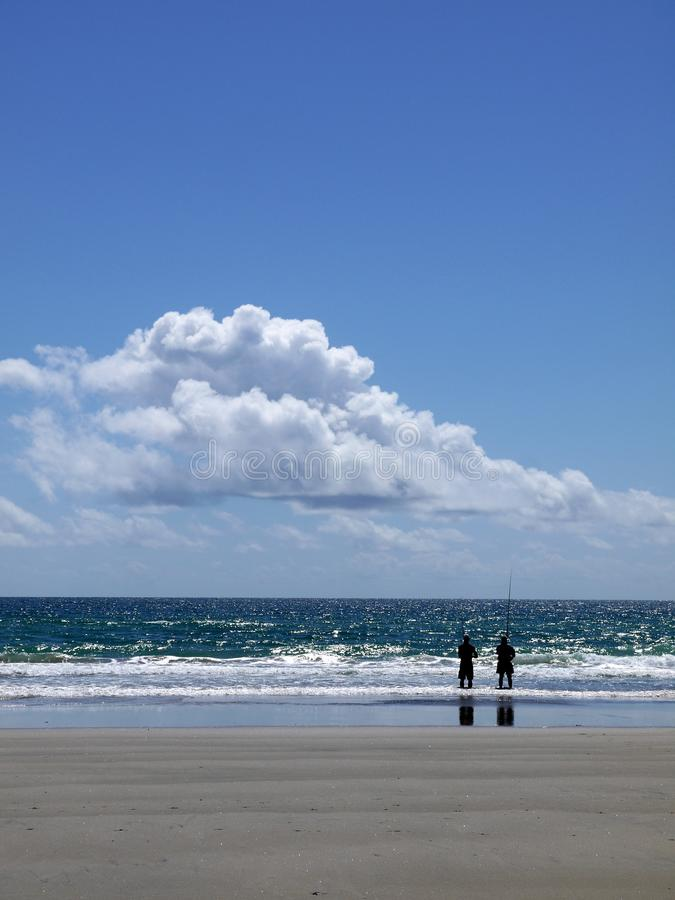 Playa: pesca de dos amigos de los hombres imagen de archivo libre de regalías