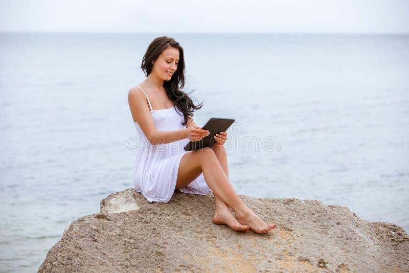 Playa que se sienta de la tecnología de Internet de la PC de la tableta de la almohadilla táctil del uso de la mujer imagenes de archivo