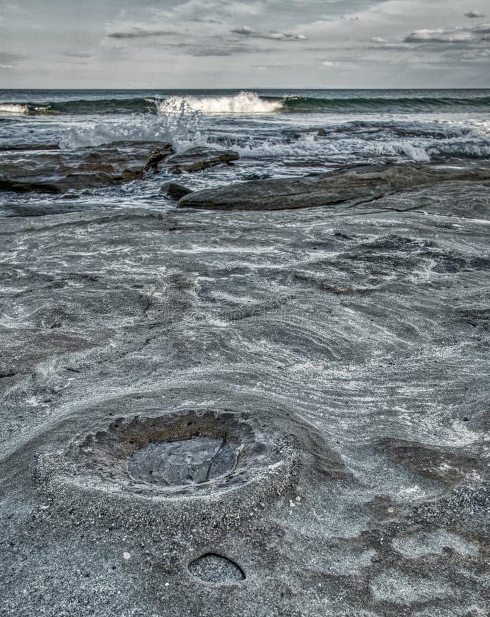Playa rocosa con el cráter de luna como superficie, ondas y nubes fotografía de archivo