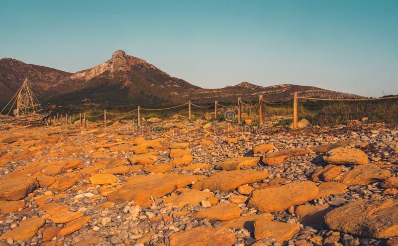 Playa rocosa del hijo Serra de Marina con el pico de montaña de Puig Ferrutx en la distancia, Mallorca, España imagenes de archivo