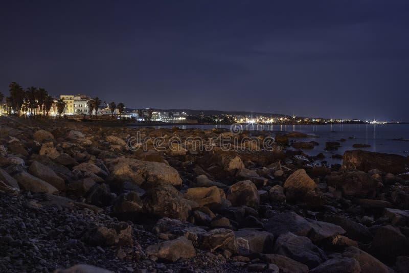 Playa rocosa iluminada por la luna Civitavecchia Italia imagenes de archivo