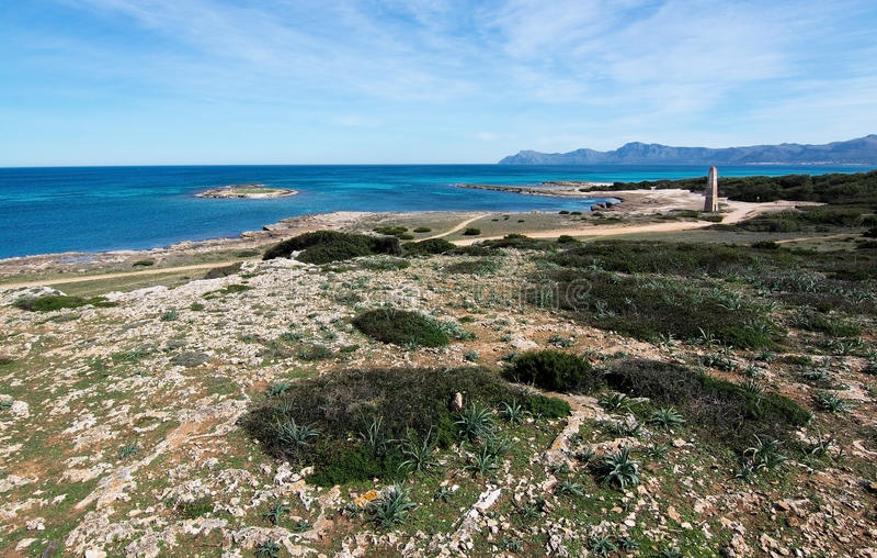 Playa rugosa con la torre vieja del reloj fotografía de archivo