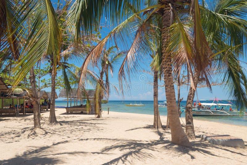Playa soleada con las palmas en la isla de Luli, bahía de Honda, Palawan, Filipinas fotos de archivo