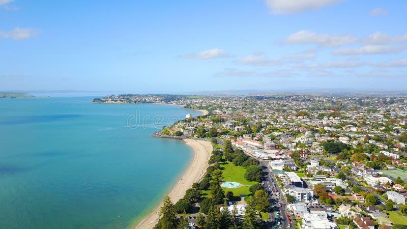 Playa soleada con suburbio residencial en el fondo Auckland, Nueva Zelandia foto de archivo libre de regalías