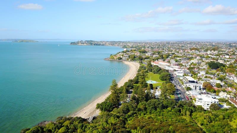 Playa soleada con suburbio residencial en el fondo Auckland, Nueva Zelandia fotografía de archivo libre de regalías