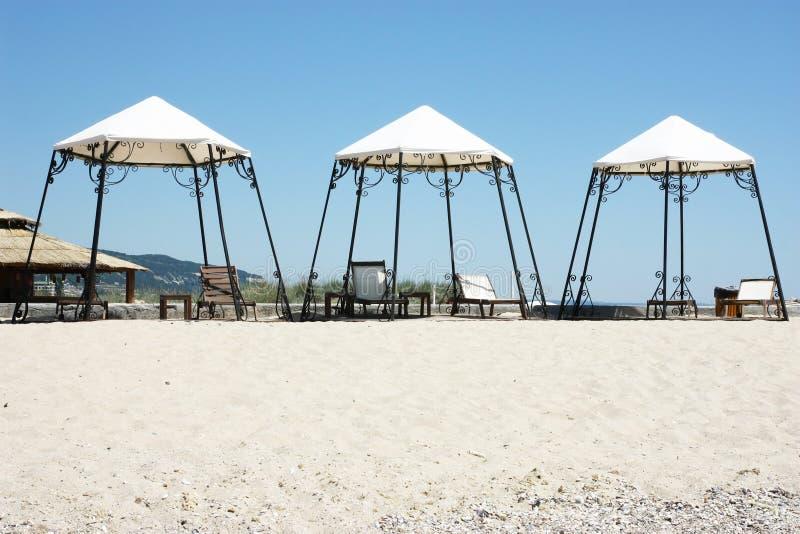 Playa soleada con 3 tiendas foto de archivo libre de regalías
