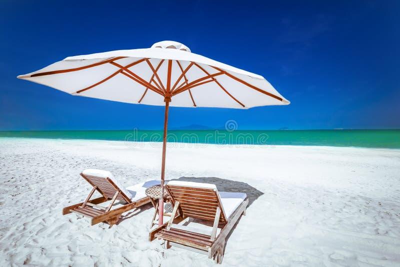 Playa tropical asombrosa con las sillas y el paraguas imágenes de archivo libres de regalías