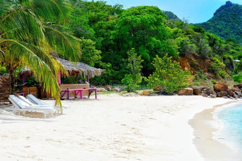 Playa tropical, casa de planta baja y agua azul imagenes de archivo